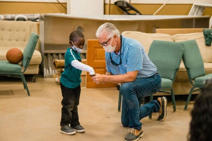 Bahamas: Abaco Islands, The Bahamas :: Logos Hopes director, Randy Grebe (USA) entertains a child at a health clinic outreach. More Info