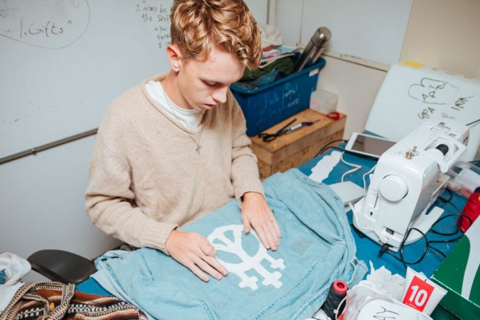 Ships: Ships :: Nathanael Wiebe (Canada) works on designing clothing during his free time on board. More Info