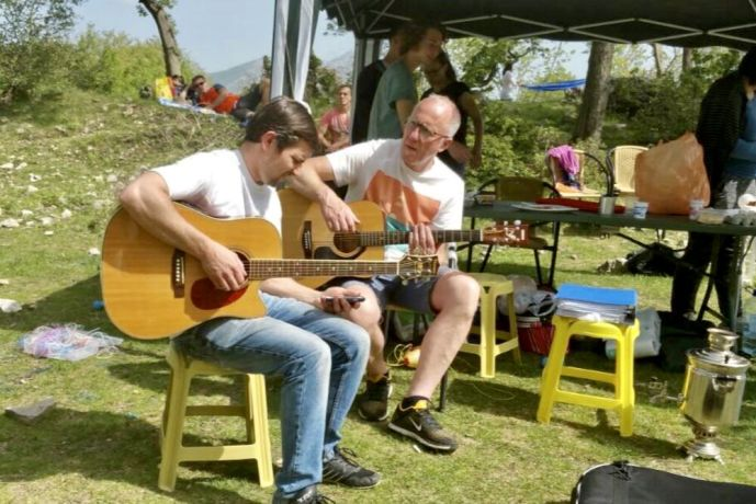Montenegro: Yan from OM Montenegro plays the guitar at a church day out in the country More Info