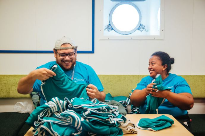 Curaçao: Caracas Bay, Curaçao :: Despite restrictions on socialising, crew find ways to bless local people. Max Albornoz (Argentina) and Rosa Maria (Guatemala) fold and separate clothes to donate to a local organisation. More Info