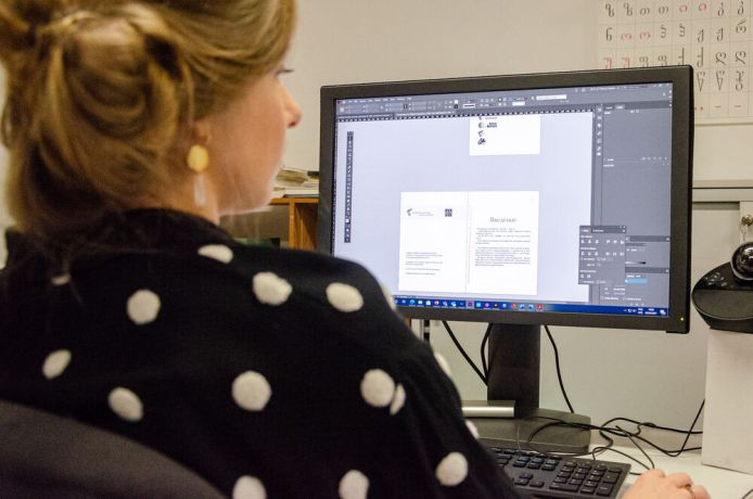 International: Graphic designer with OMs media ministry working on a publication layout. More Info