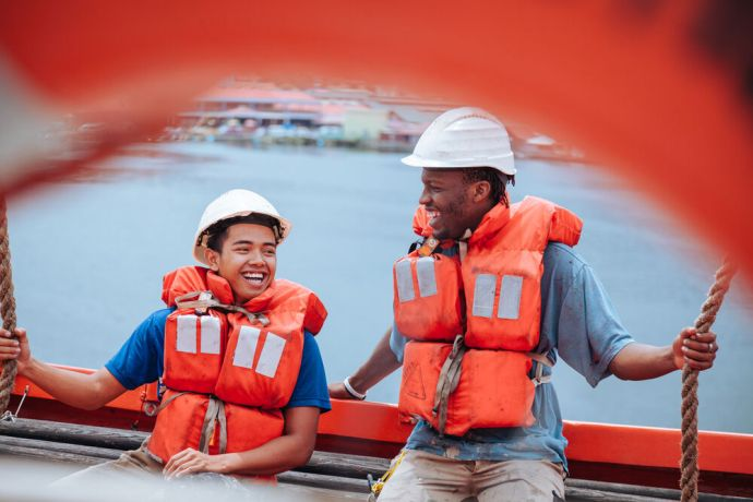 Saint Lucia: Castries, Saint Lucia :: Ezra Williams (Indonesia) and Siza Mafuxwana (South Africa) from the deck department in a lifeboat during a drill. More Info