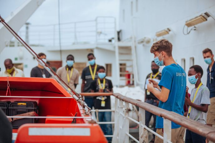 Saint Lucia: Castries, Saint Lucia :: Marco Valerio (Argentina) explains the lifeboats to a group of boys visiting the ship. More Info