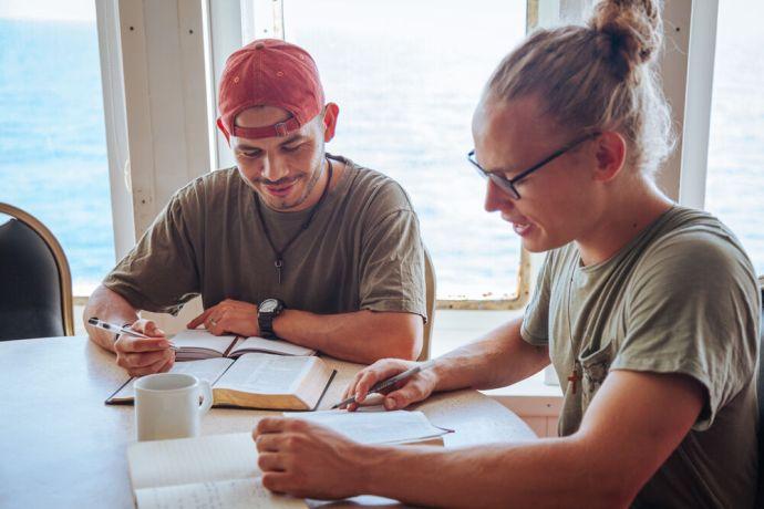 Ships: OM Ships :: Jareht Gradiz (Nicaragua, left) studies the Bible with Tim Haeger (Germany, right) on board Logos Hope. More Info