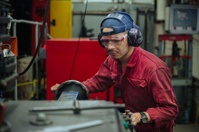Ships: OM Ships :: Jareht Gradiz (Nicaragua) works on a machine in Logos Hopes engine room. More Info