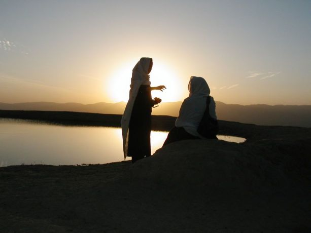 Central Asia: Silhouette of two women by water. More Info
