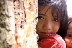 A young Thai girl shyly glances at the camera.
