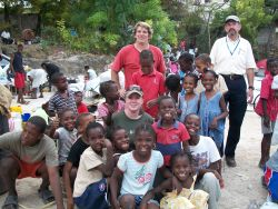 Three people from a US team in Haiti with children at an orphanage.