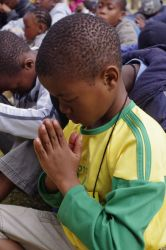 Children pray during an outreach.