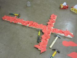 The cross filled with red notes symbolising past pain, wounds and sin.