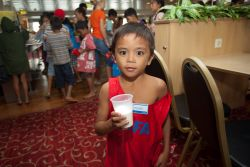 Cebu, Philippines :: A street kid drinks a glass of milk in the dinner room.