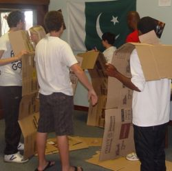 Youth in East London making cardboard signs for street ministry outreach.