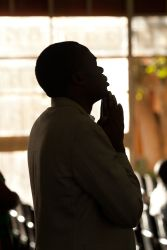 A Zambian man holds his hands together in prayers during a gathering for the Global Day of Prayer.  Members from several congregations across Kabwe, Zambia came together for this important day.