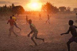 Children in the village of Mussa playing soccer barefoot at sunset.