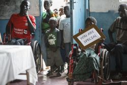 A disable girl in a wheelchair holding a You are special sign. OM Zambia started the first school for disabled children in Kabwe in January 2013.