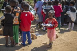 A young girl at Makwati school is handed her first school lunch.