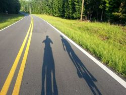 Shadows of Dustin and Katie Kelms of OM Arts, riding unicycles across the US this summer 2013 in aid of Syrian refugees and displaced people
