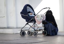 Conservative Muslim woman sits with her child in the shade of the mosque in North Africa.  