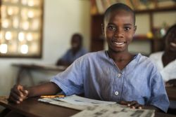 A student poses for a photo at the GOOD NEWS II Orphan School run by OM Lake Tanganyika.