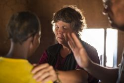 Nurse Lenie Coetzer prays for a woman during a medical outreach to Nsovwe village.
