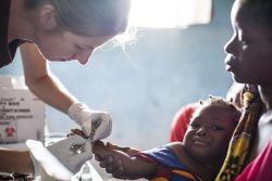 Nurse Nicky Tiltman with baby patient, Lake Tanganyika