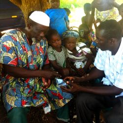 Chris explains how to use an AudiBible to a local Muslim village leader.