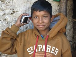 A young boy uses a mini-SD card with the New Testament in his radio to listen to the book of Matthew for the first time in Mugu, Nepal.