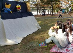 An OMer is doing a puppet show for children at a park nearby a church in Matto (Ishikawa), involving local church members and a visiting short term team