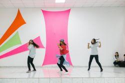 Three girls take part in an OM Arts dance performance in a church during an outreach.
