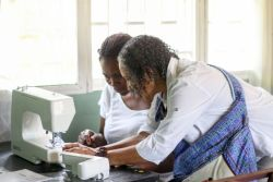 Maputo, Mozambique :: Sonia Madder (Brazil) teaches a deaf woman sewing techniques on the new machines donated from Logos Hope to Hands that Talk, a charity deaf school.