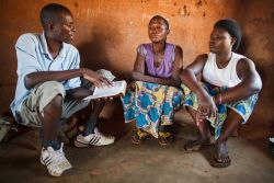 Charles Chansa sharing the gospel to two woman in a village on Lake Tanganyika