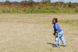 With the aid of crutches and leg splints provided by Bethesda Mercy Ministries, nine-year-old Yande walks across a field.