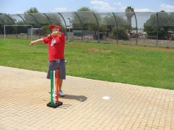 Andre Kotze, OM South Africa SportsLink, demonstrates a bowling action to youth at a development centre