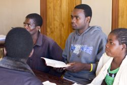 Kelvin, centre in grey, listens in Discipleship class in Malawi. Previously a follower of Islam, Kelvin came to know Jesus through OM Malawis prison ministry (he was being held because a friend had stolen wood, not because of anything he had done).