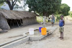 Two girls pump water from the OM borehole in Chisopi.