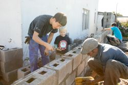 Cape Town, South Africa :: KyungYun Seo (South Korea) helps a local handy man to put up a wall at a local orphanage.