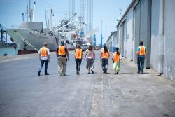 Tema, Ghana :: Logos Hopes crewmembers walk through the Tema port to visit other ships.
