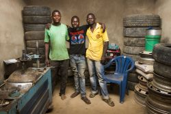 Brian, centre, stands in the middle of his mechanic shop with the two men he is discipling and training. Brian was discipled at the OM base in Mpulungu and encouraged and empowered to go to technical school after graduation. Having experienced the value of being discipled, Brian is in turn discipling others.