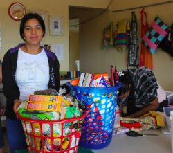 Women of the Jewel of Hope ministry of OM Panama fill two baskets with food and houshold items to bless a mother in need.