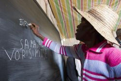 A woman proudly writes her name on the blackboard at a school opening. The one-roomed school was built by the community itself. OM has been building a relationship with the village over the past few months through fellowship and trainings. One of those trainings was Literacy training which two of the local ladies took up and started under a tree with 20 students of all ages.
