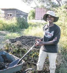 Moses building a compost pile at OM Zambia model farm