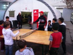 an OMer teaches young refugee friends how to play table tennis