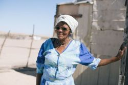 A Topnaar lady In Namibia standing by her house.