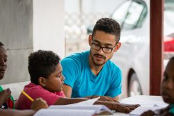Port of Spain, Trinidad  Tobago :: Miguel Amaro (Brazil) helps a boy with his homework.