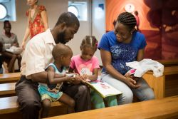 Kingston, Jamaica :: A family visiting the ship reads a book they purchased on board in Kingston, Jamaica.