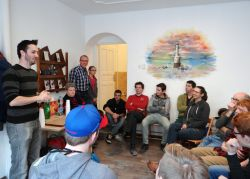 OMer Frans (far left) speaks to friends and team members including fellow OMer Marcel (corner; plaid shirt) at the opening celebration of the DOCK community centre in Hungary.