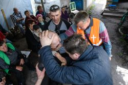 An elderly man is anointed with oil during a church service within the conflict zone of eastern Ukraine.  Photo by Garrett N