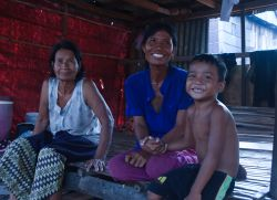 A young boy and his mother and grandmother sit in the kitchen area below their bamboo and tin home, that MTI Cambodia built for them.