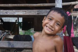 A young boy sits on the ladder up to his bamboo and tin home, that MTI Cambodia built for them.