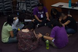 A group gathers together to pray for each other during Out of the Comfort Zone Asias opening night service.